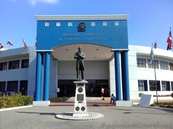 Dirección General de Migración and the statue of Juan Pablo Duarte at the front entrance.