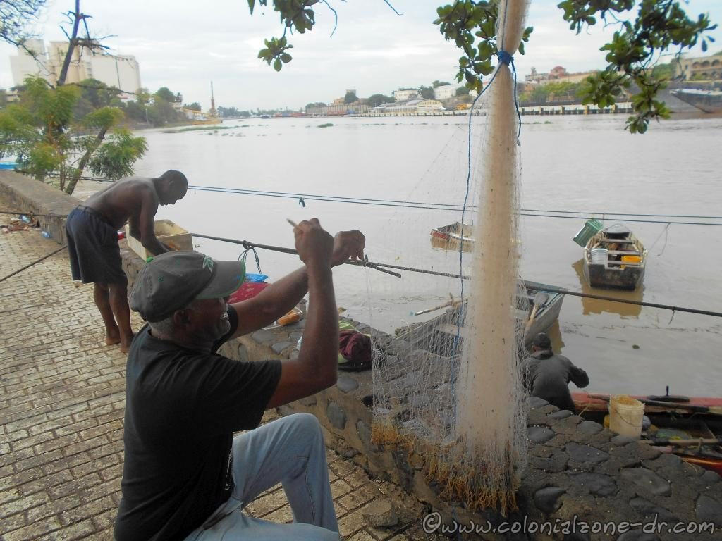Fishermen repiring his nets as the others are preparing to head out to the Caribbean Sea at the entrance to Rio Ozama.
