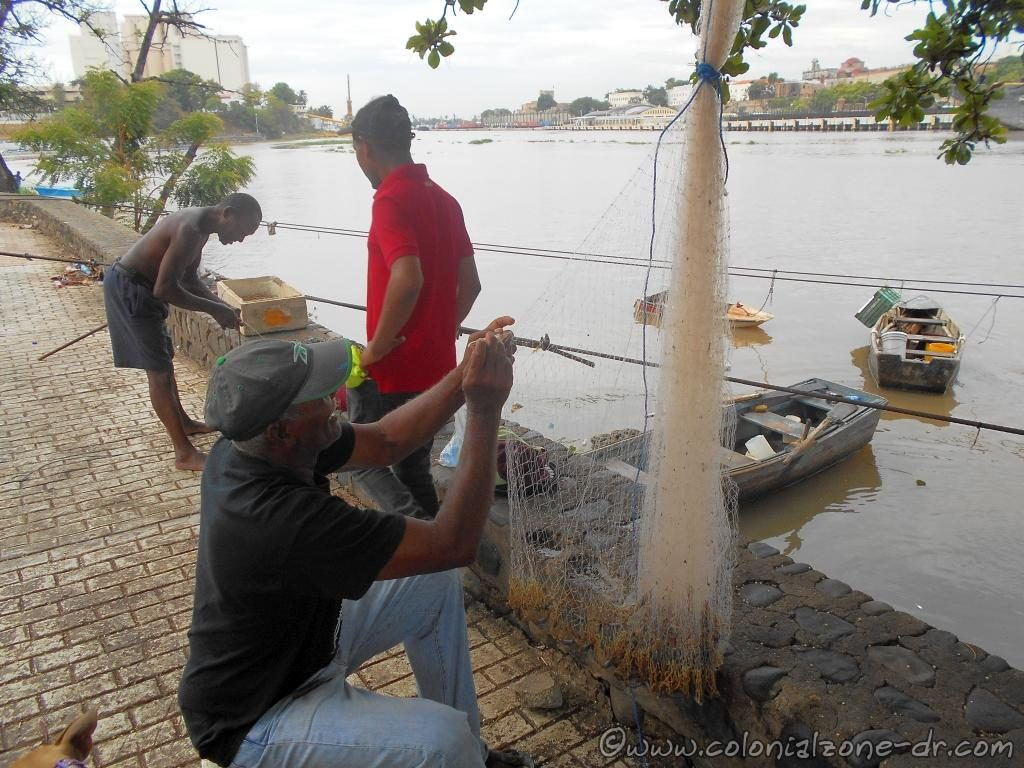 Fishermen repairing his nets preparing for a day of fishing on the Caribbean Sea at the entrance to Rio Ozama.