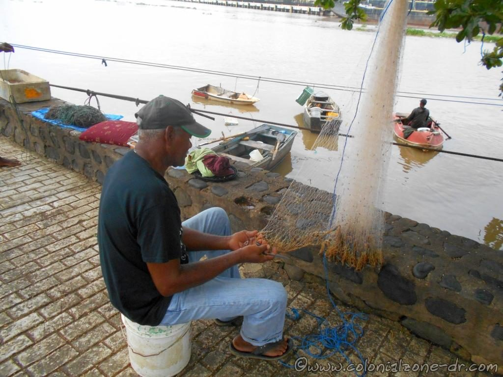 Fisherman on Rio Ozama repairing nets with skill, moving the shuttle and tying the knots.