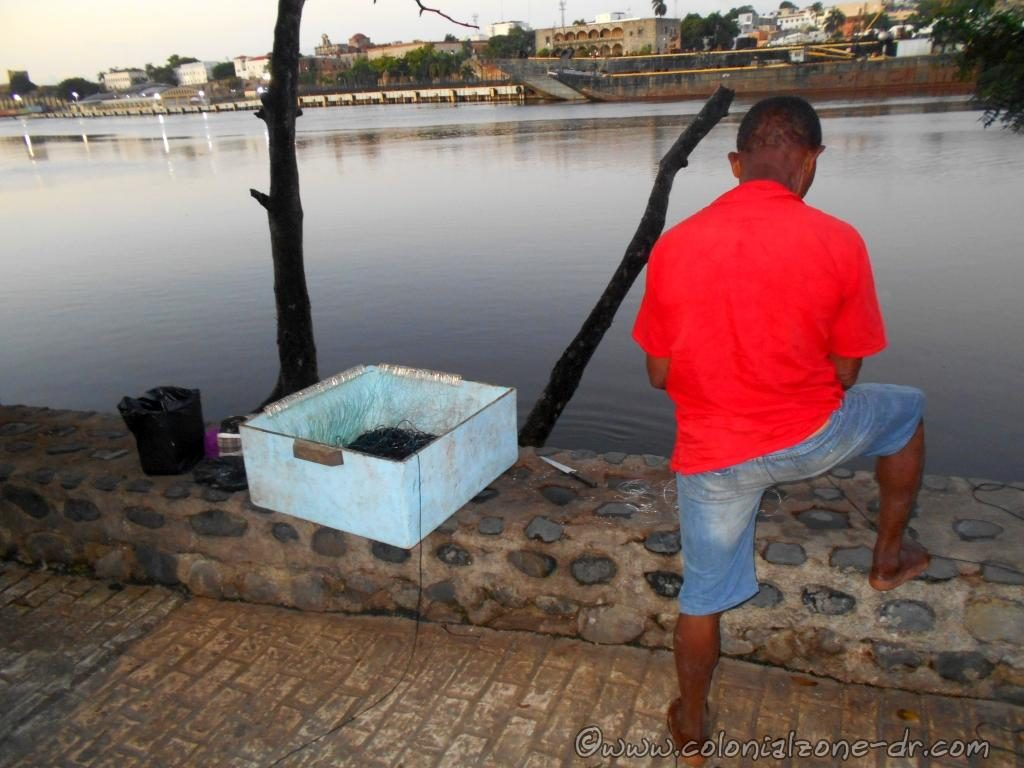 Fisherman at Puente Flotante along Rio Ozama straightening out his lines