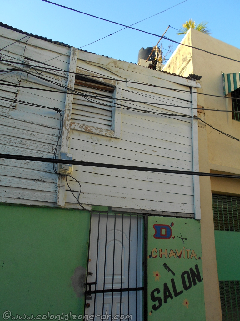 A black cat watching us from its perch atop a zinc rooftop in Barrio San Antón.